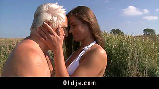 Charming busty teenager in white bikini fucks an aged man in the field