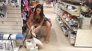 Lovely slender amateur girl flashes her pussy in the shoe shop
