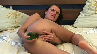 A solo girl is ramming her ass with a large dildo on the bed