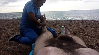 Lucky guy has a sexy lady massaging his feet on the beach