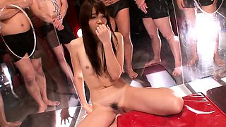 Pretty Oriental babe works her sexy lips on a gang of cocks