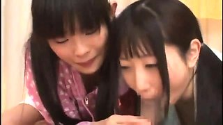 Two adorable Japanese schoolgirls take turns on a stiff cock