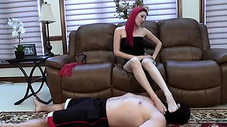 Hot redhead mistress dominates her slave with her sexy feet